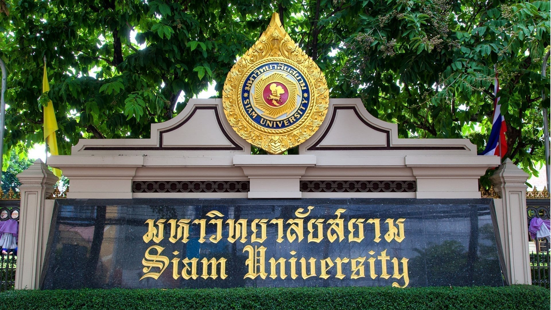 A picture of the name plate of Siam University written in Thai and English and a golden symbol on top in Bangkok..