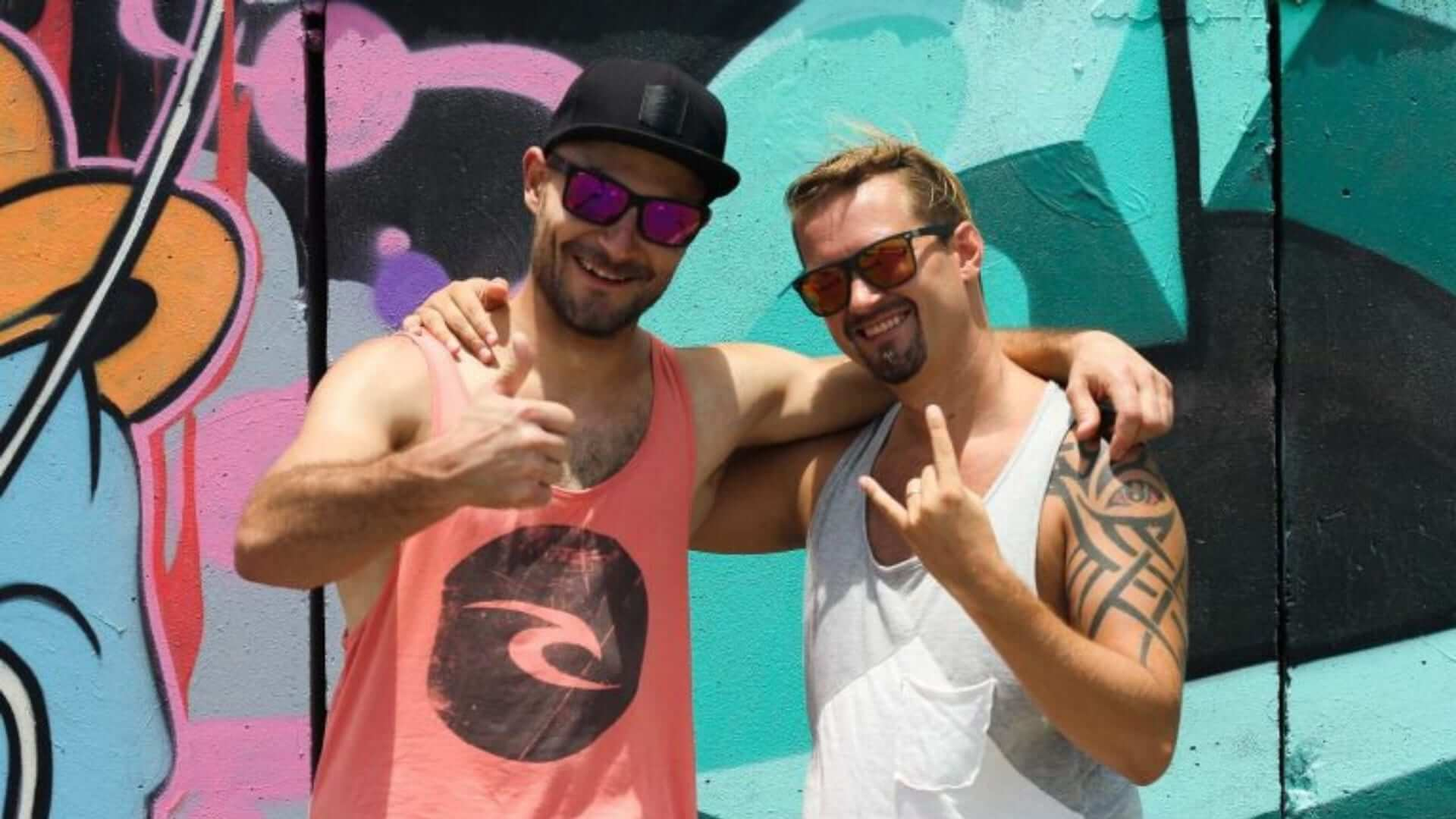 Two man who are wearing sunglasses and tanktops are embracing eachother and making hand gestures in front of a graffiti wall in Bali.