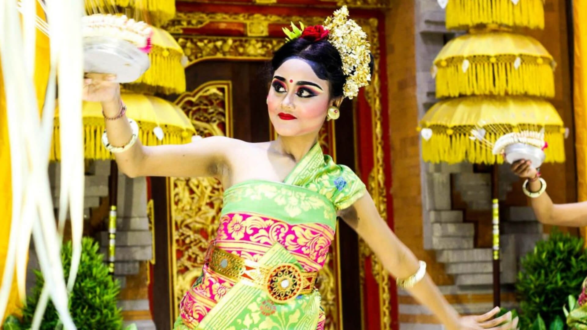 A woman in Balinese traditional clothes is dancing in front of a temple in Bali.