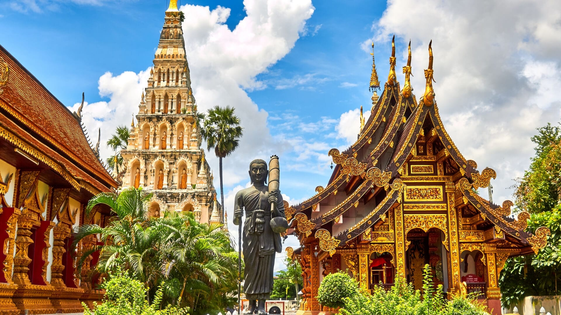 A statue and different temples during a day in Thailand.