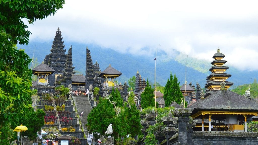 The roofs of the Balinese temples with a foggy mountain in the background.