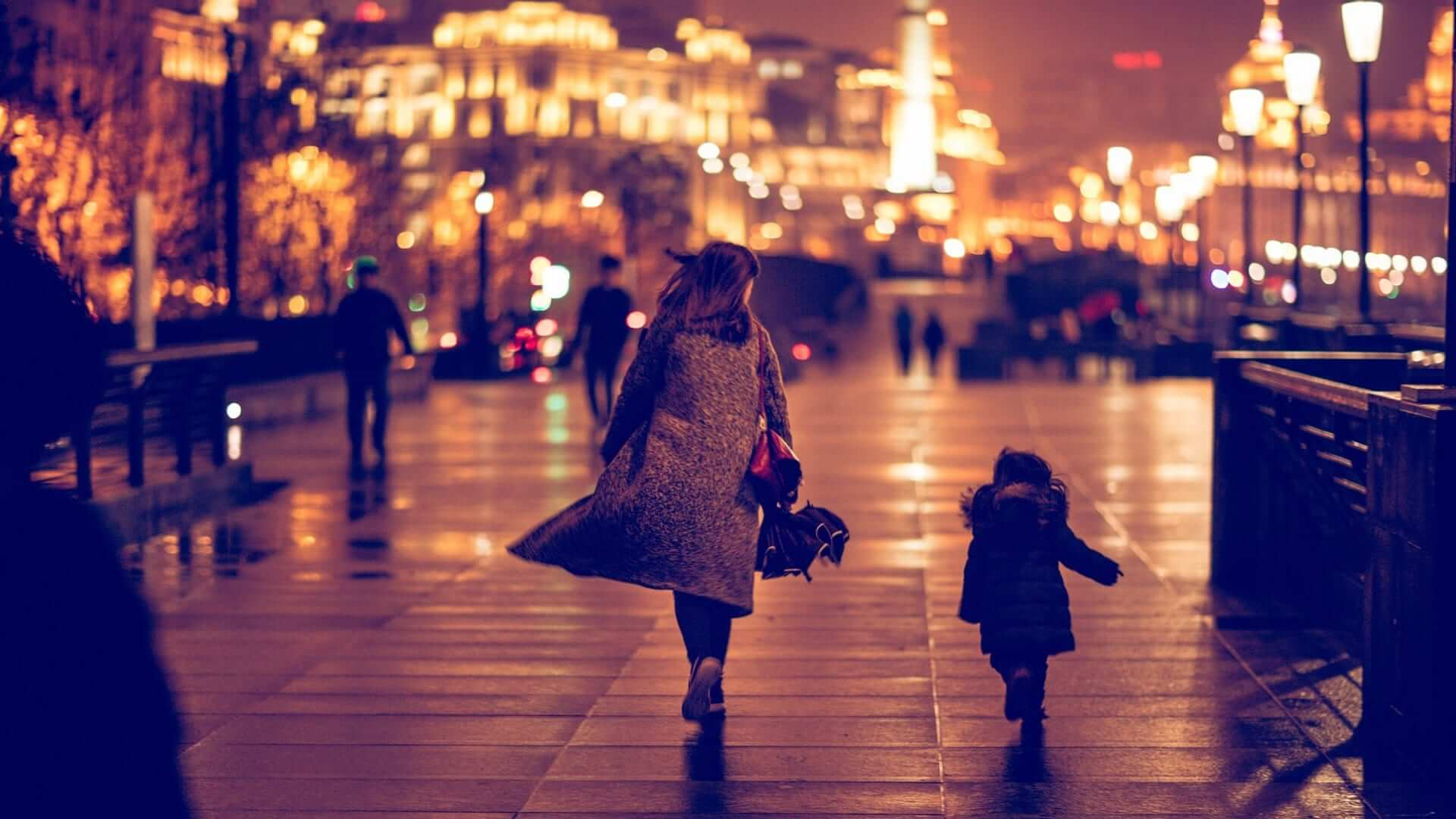 A woman and a child are running on a quay towards an illuminated building on a rainy evening in Shanghai.