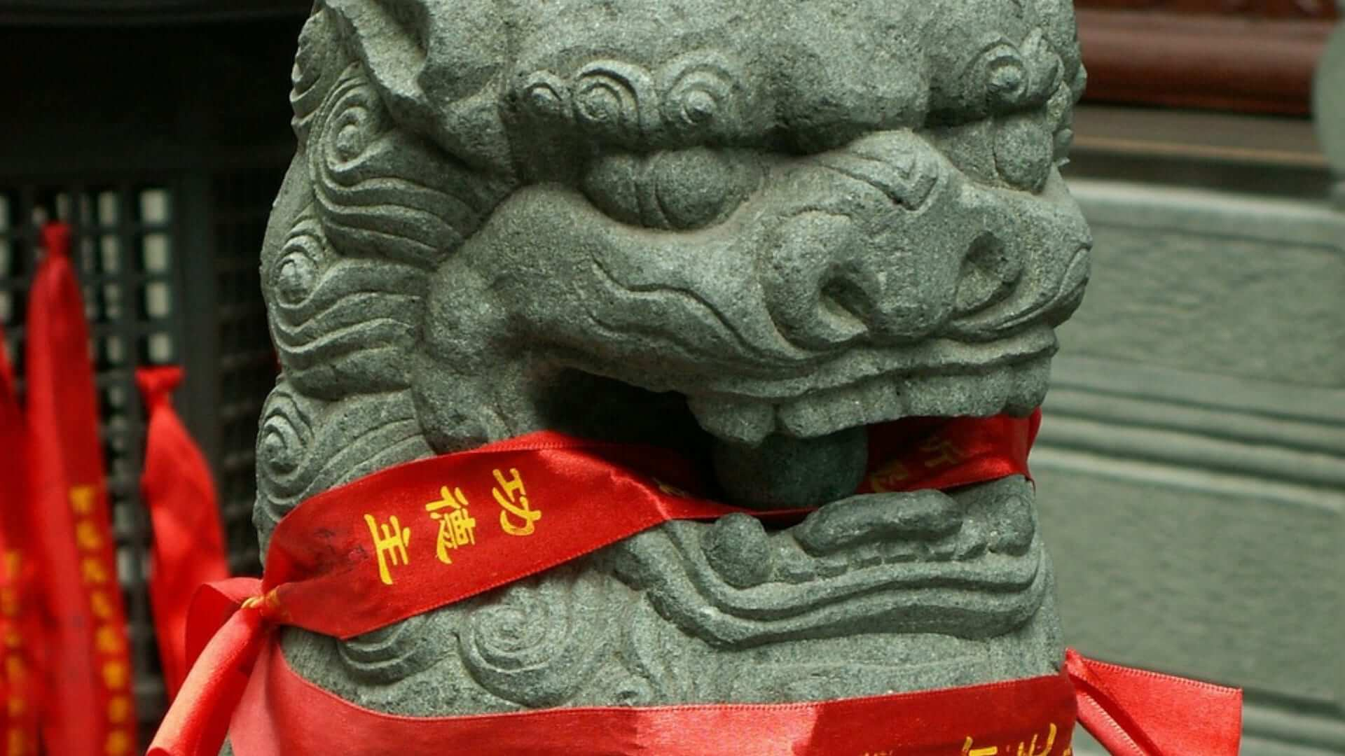 A Chinese lion made of stone with a red ribbon in his mouth at a temple in Shanghai.