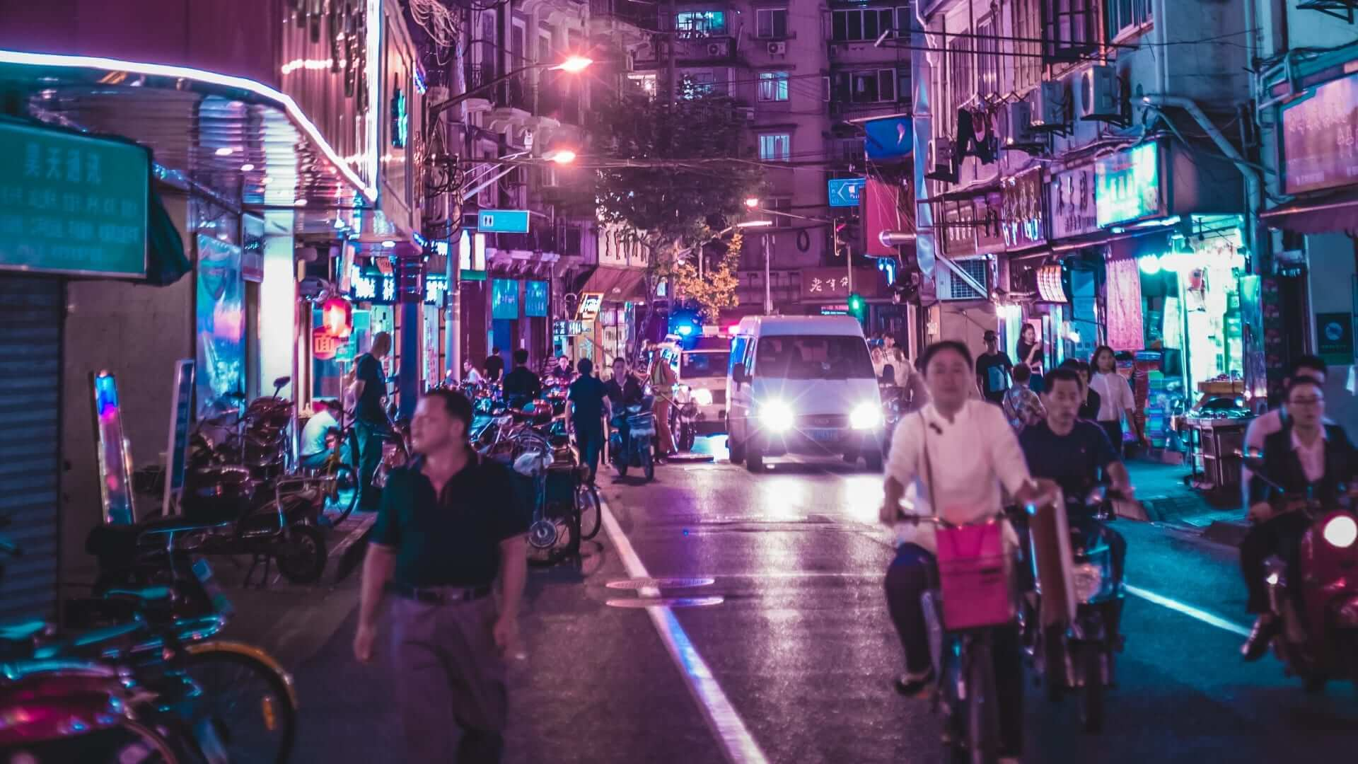 People are walking, riding a bicycle or driving a car in a street during night in Shanghai.