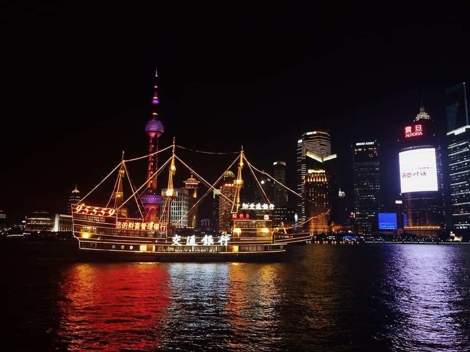 An illuminated boat is laying in a river surrounded by illuminated buildings in Shanghai