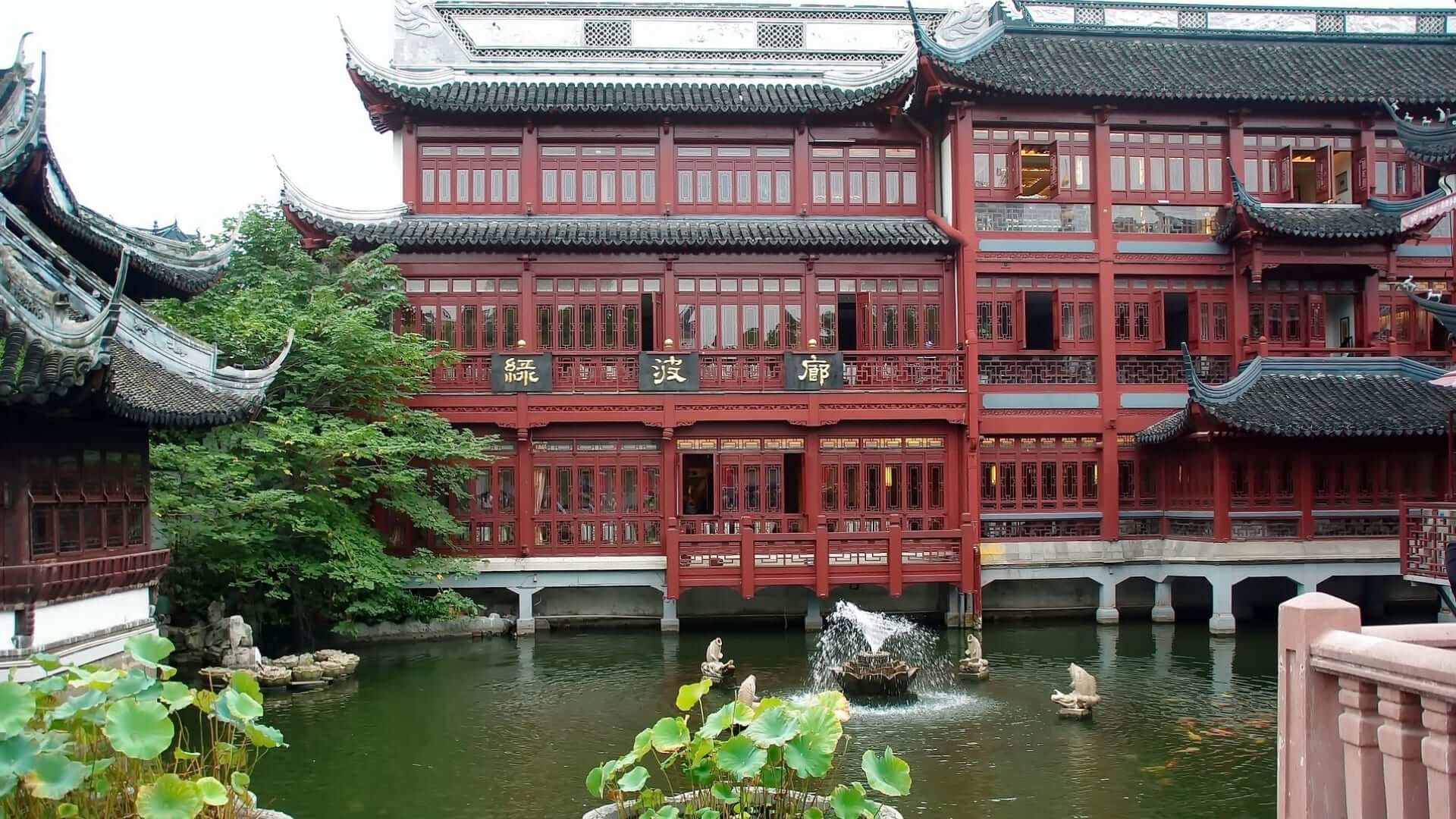 A red big Chinese house is standing in water in a park in Shanghai.