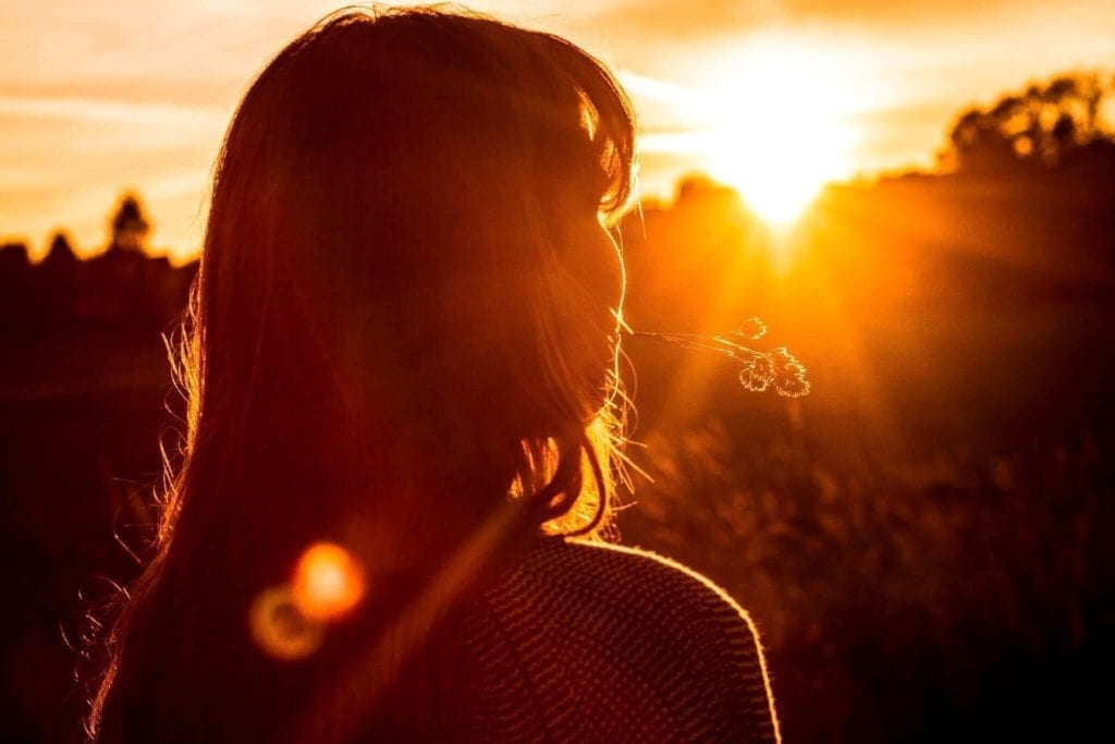 Girl holding straw in her mouth while enjoying the sunrise