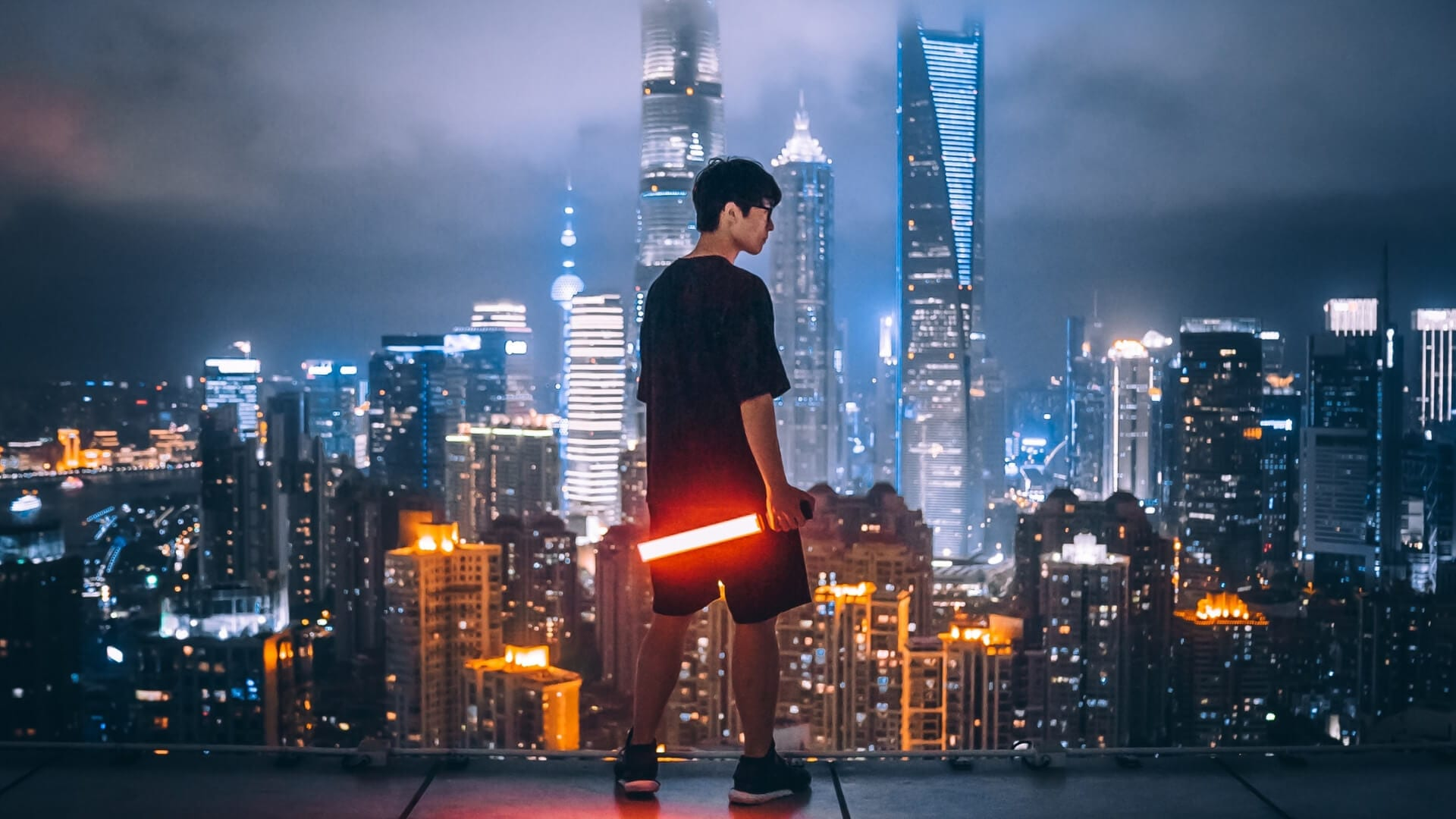 A boy is standing on a high building in Shanghai while he is looking over the city and holding a red stick during a night in Shanghai.