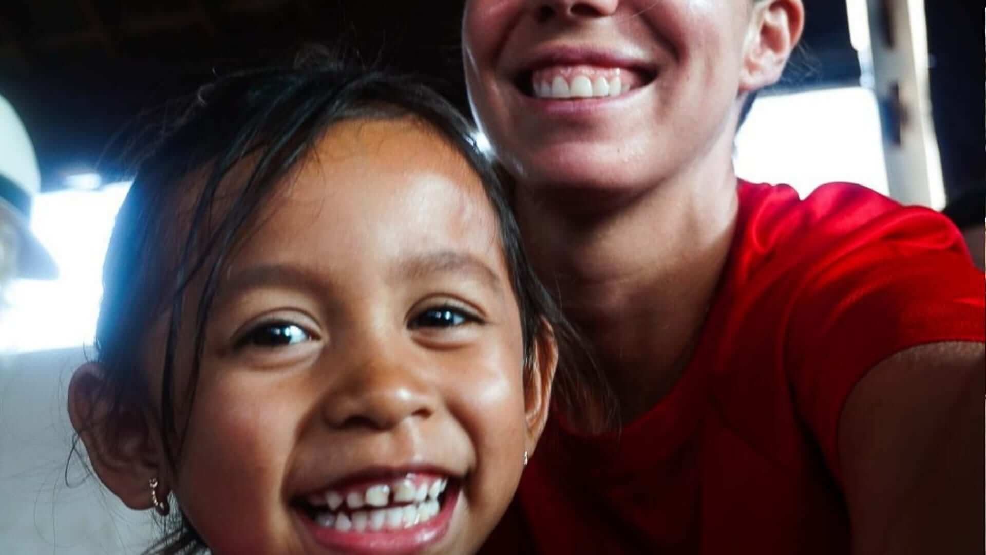 An Indonesian orphan is smiling into the camera and behind her is a western girl smiling.