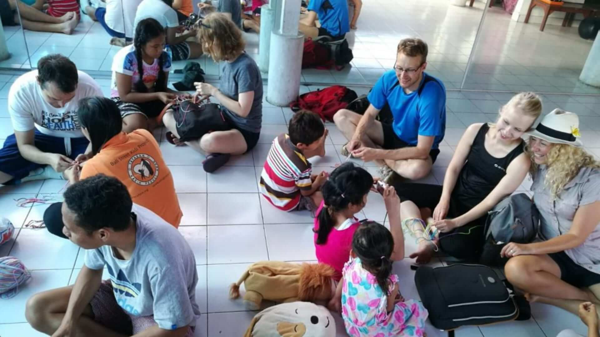 A group of people is sitting on the floor making bracelets with eachother in Bali.