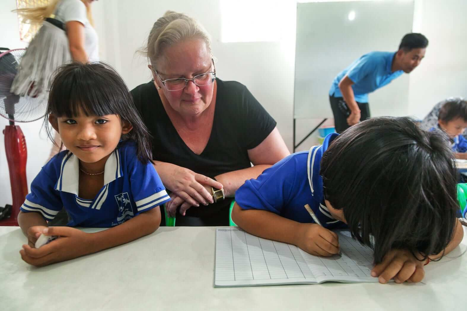a woman is teaching two kids to write