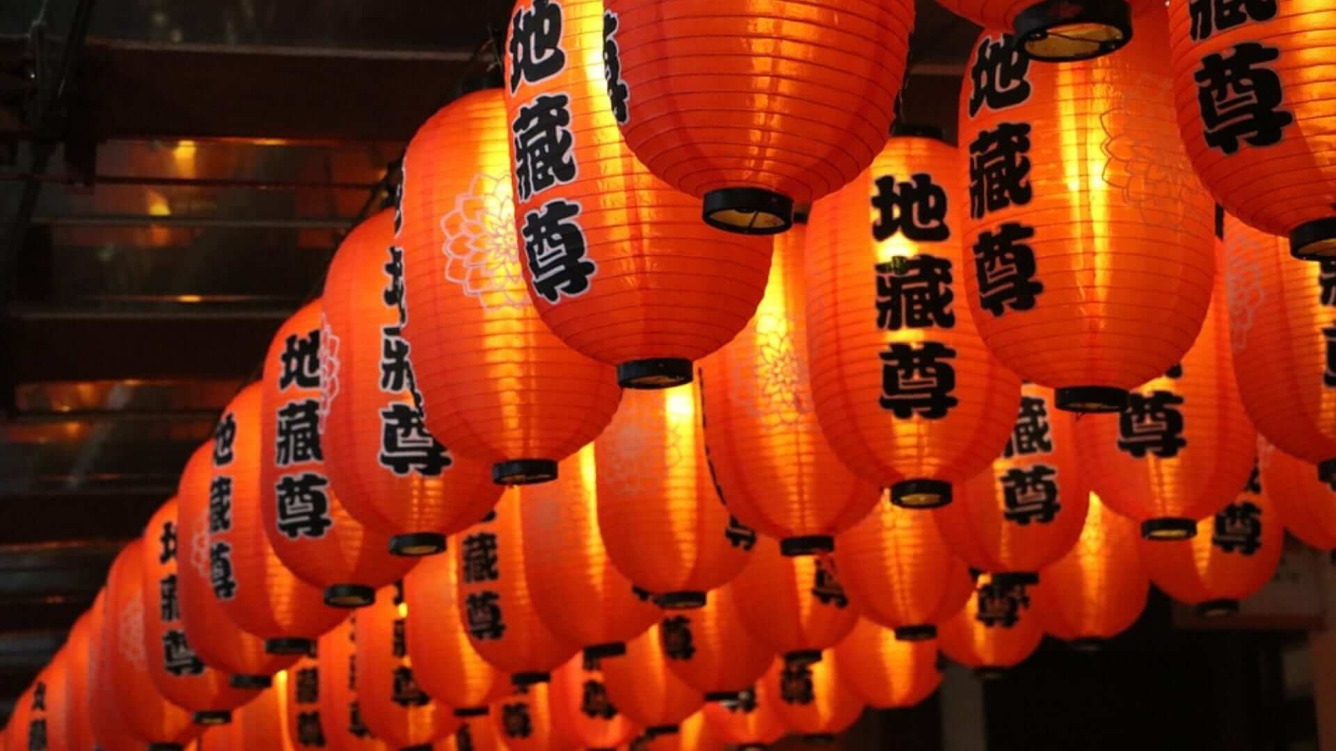 Many illuminated red lanterns with Chinese characters on them during a festival in China.