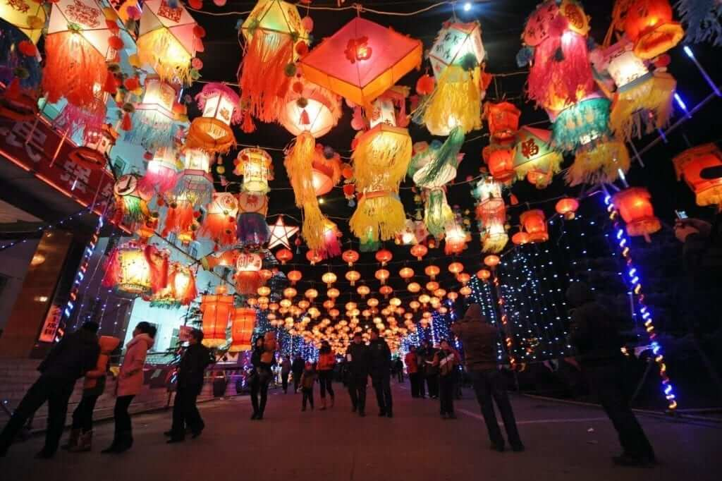 colorful lighted lanterns are hanging on the streets
