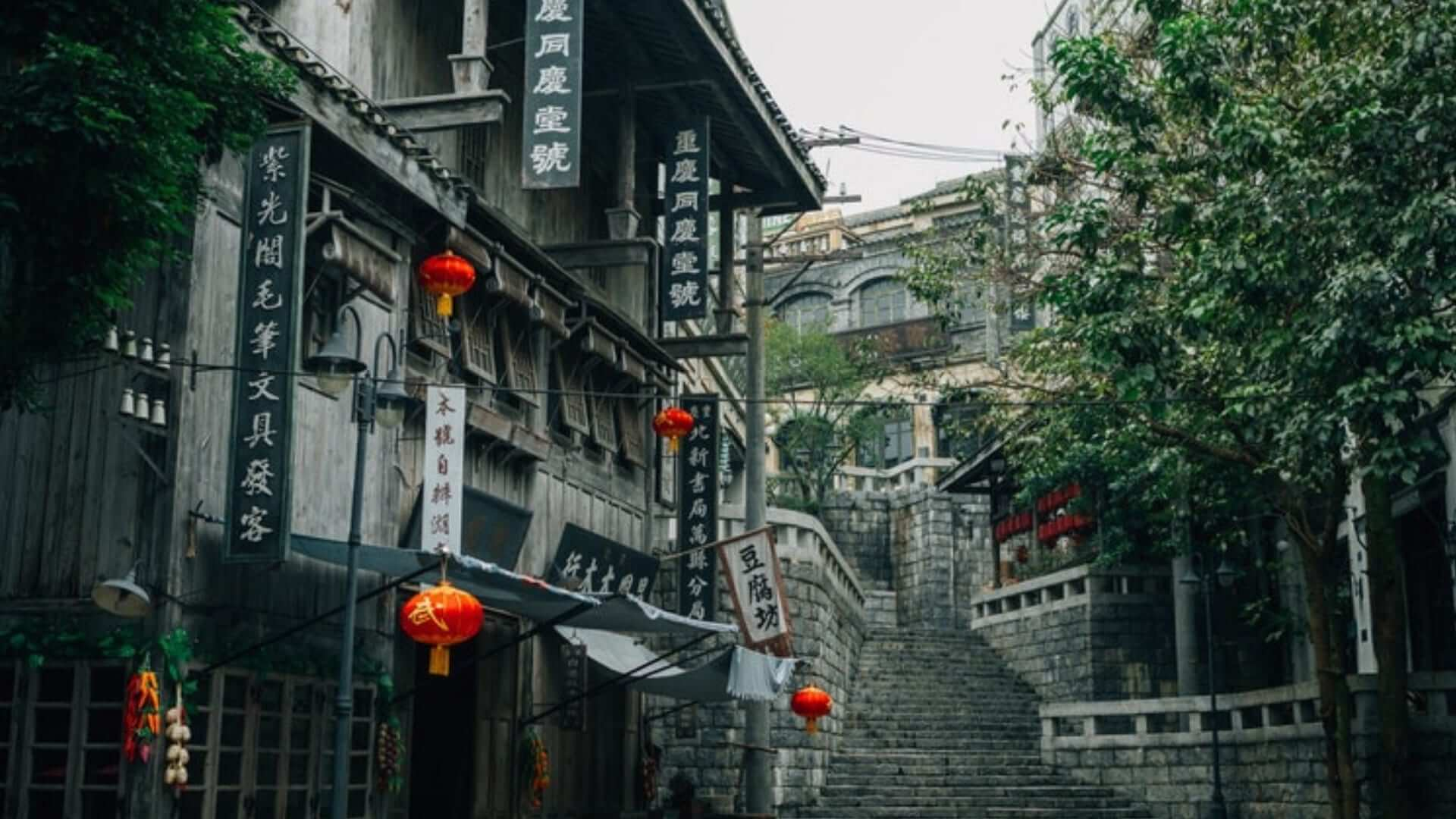 Red lanterns and plates with Chinese characters are hanging on a building in a street with a staircase in China.