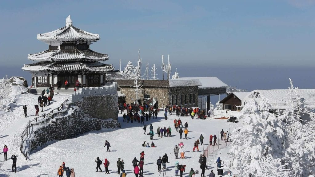 Traditional Korean village during olympics with a temple at the top of a hill