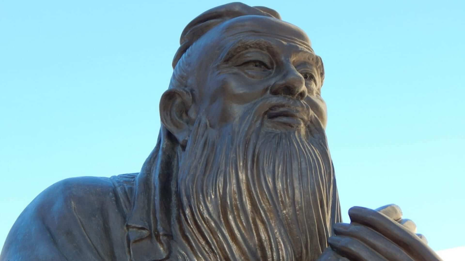 A statue of an old man with a long beard and a blue sky China.