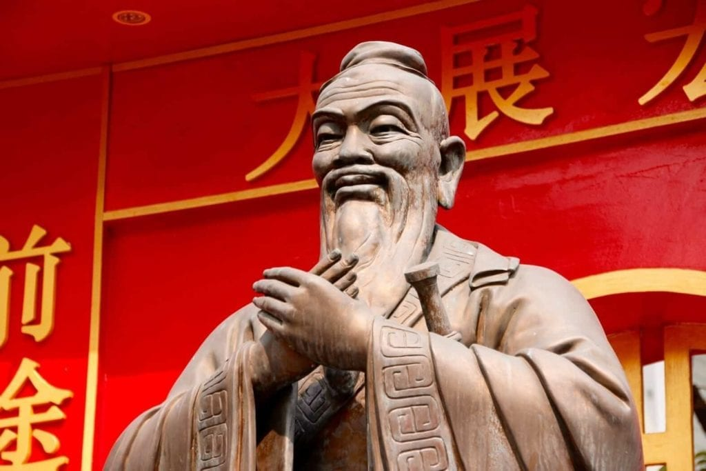 Statue of confucius chinese philosopher and founder of confucianism with gold coloured chinese characters at the back and red background