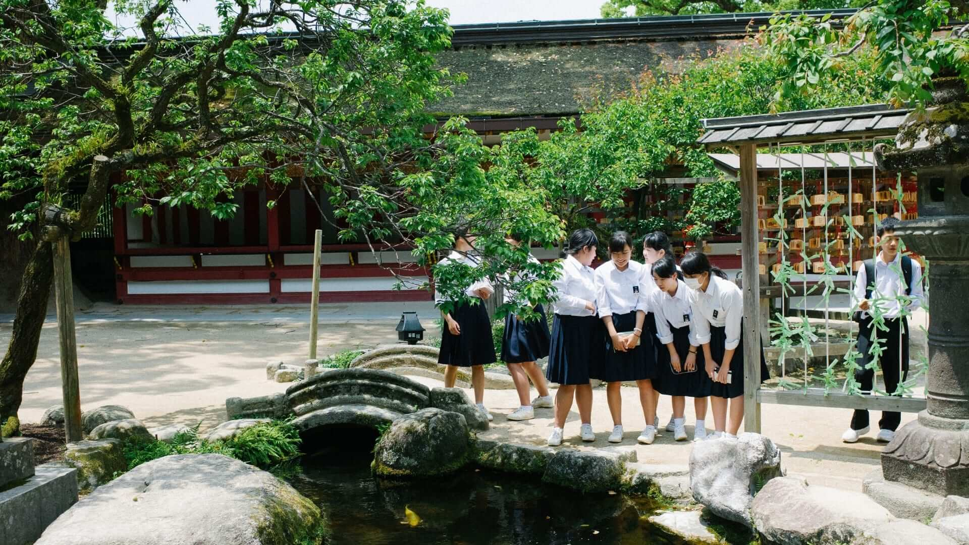 A group of female students wearing school uniforms is looking into a pond with a fish swimming in it in Japan.