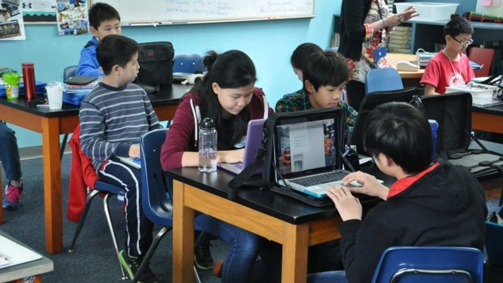Chinese children are studying on laptops in a classroom in China.