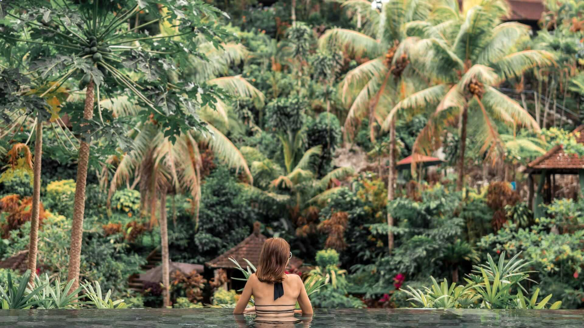 A person is sitting in a infinity pool and looking at green palm trees in Bali.