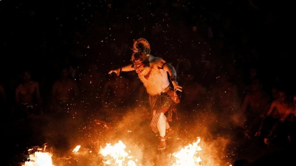 A man wearing hanuman white monkey costume is dancing in front of a fire as part of a Balinese ceremony at a temple in Uluwatu.
