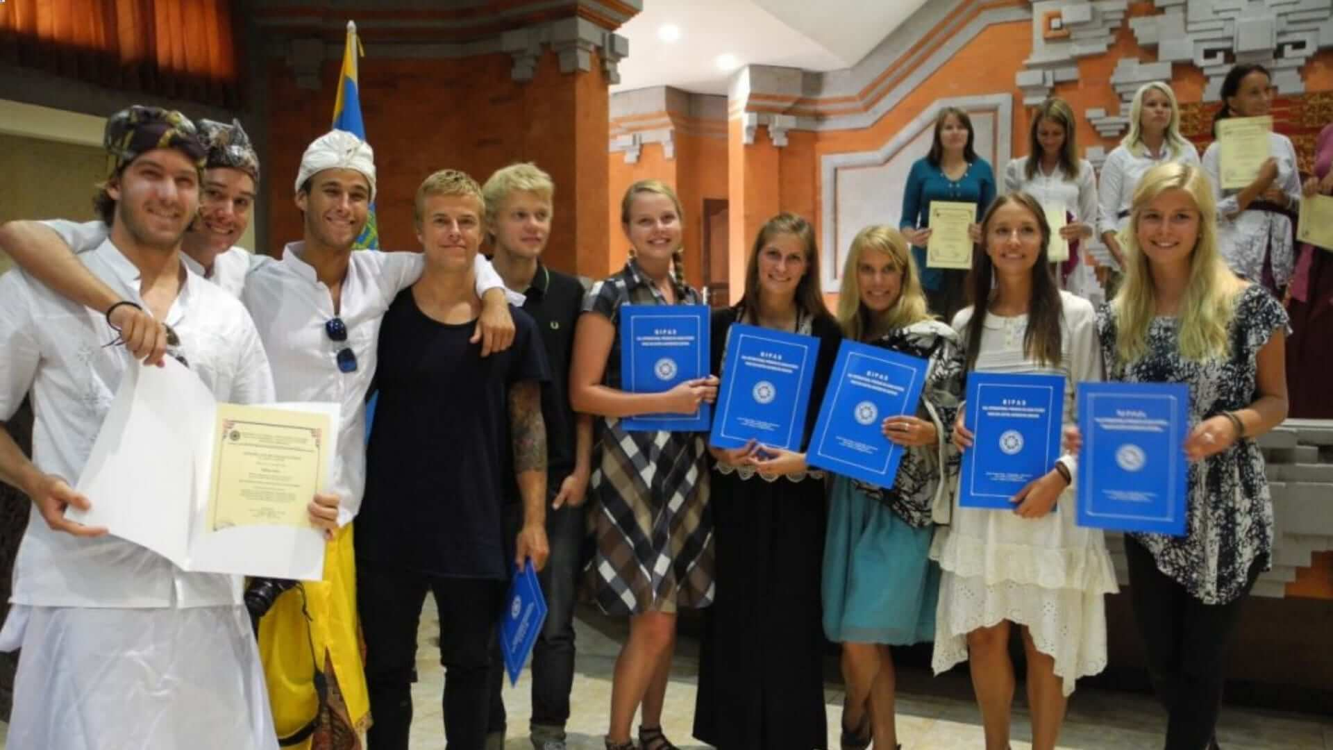 Students are holding a blue certificate at an Indonesian university in Bali.