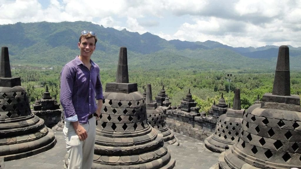 a man in polo standing beside a bell like statue in Borobudur Temple