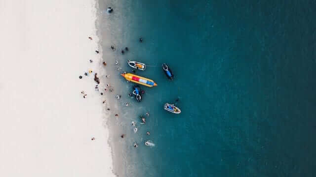 drone foto from a white sand beach and watersport equipment in the water.