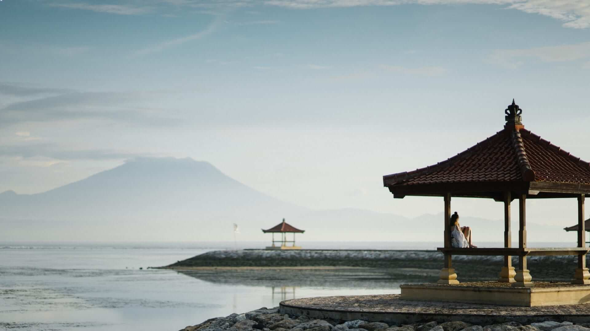 A person is sitting on a gazebo next to the water during sunrise in Bali.