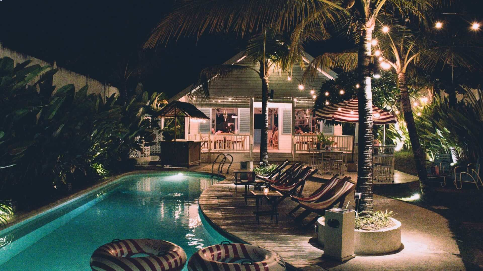 A pool with chairs next to it at a villa during night in Bali.