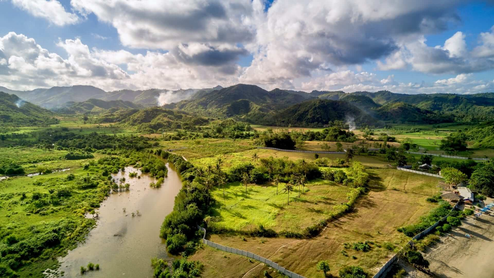A river, green grasslands and hills during a claudy day in Lombok.