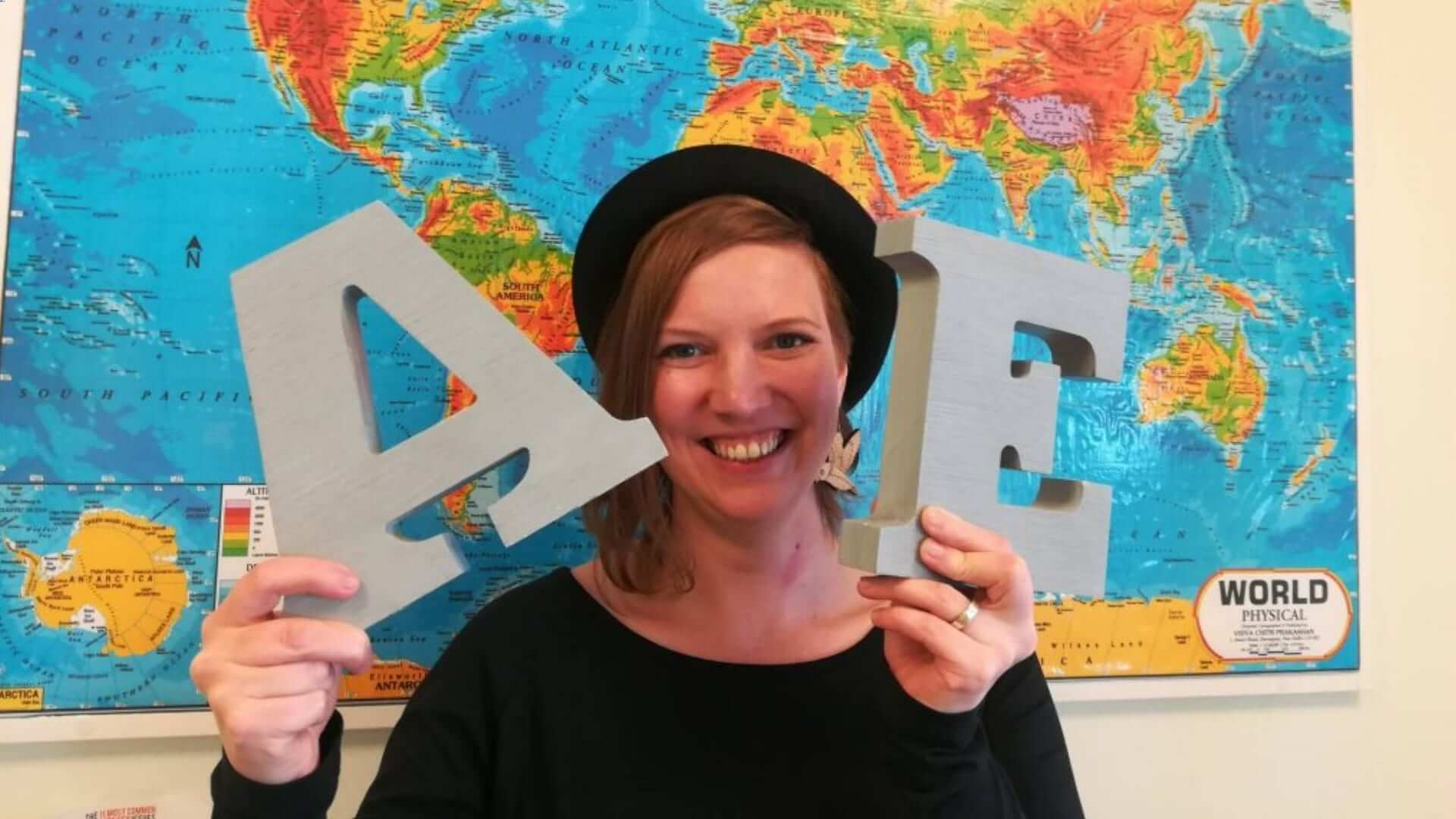 A woman is standing in front of a map holding two letters (A and E) and is smiling.
