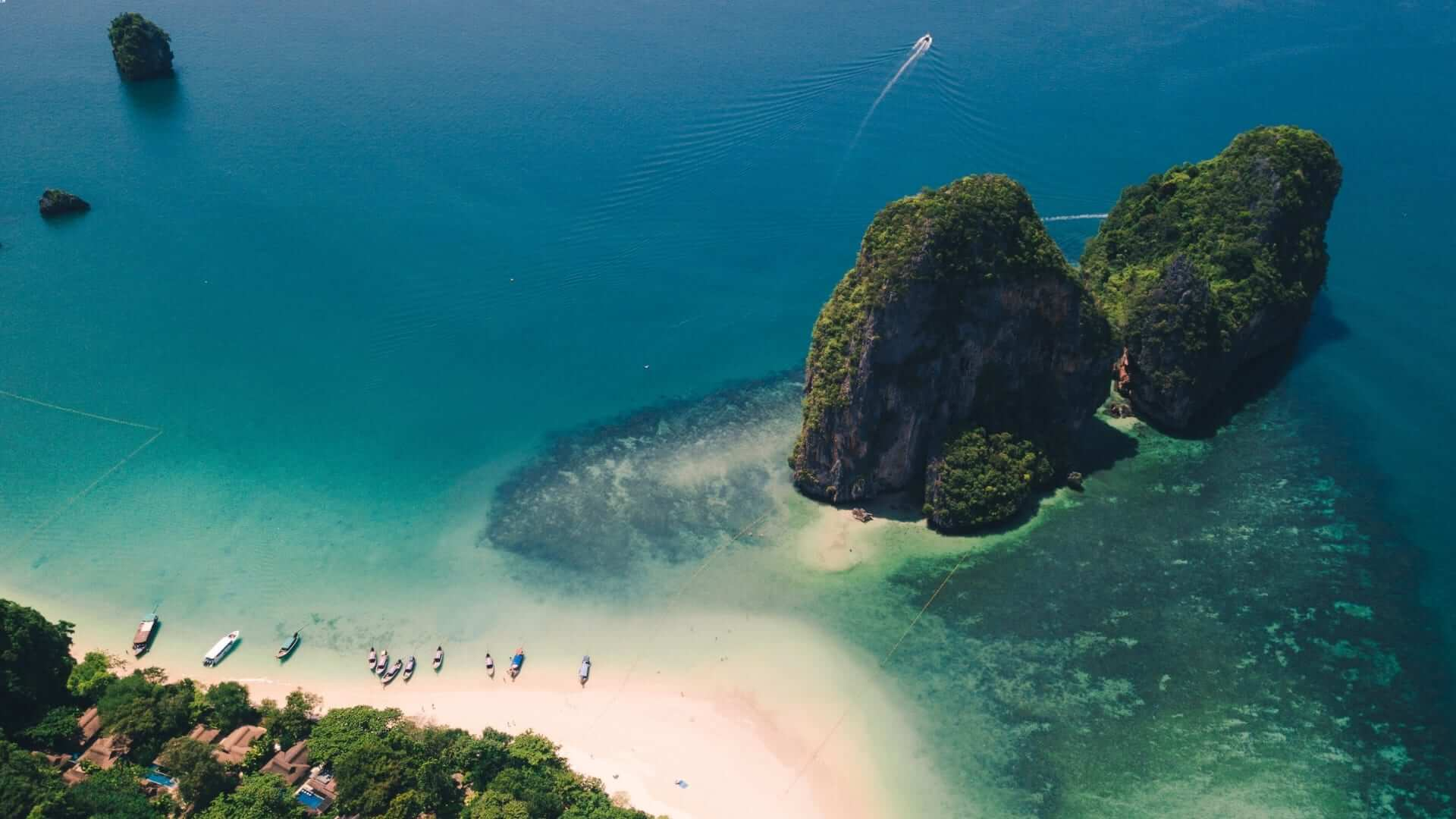 A small island next to a white beach and blue water in Thailand.