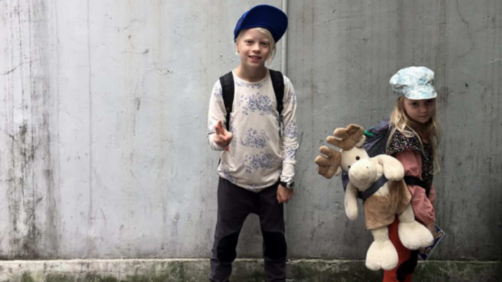 A blond boy and a girl are standing in front of a grey wall in Shanghai.