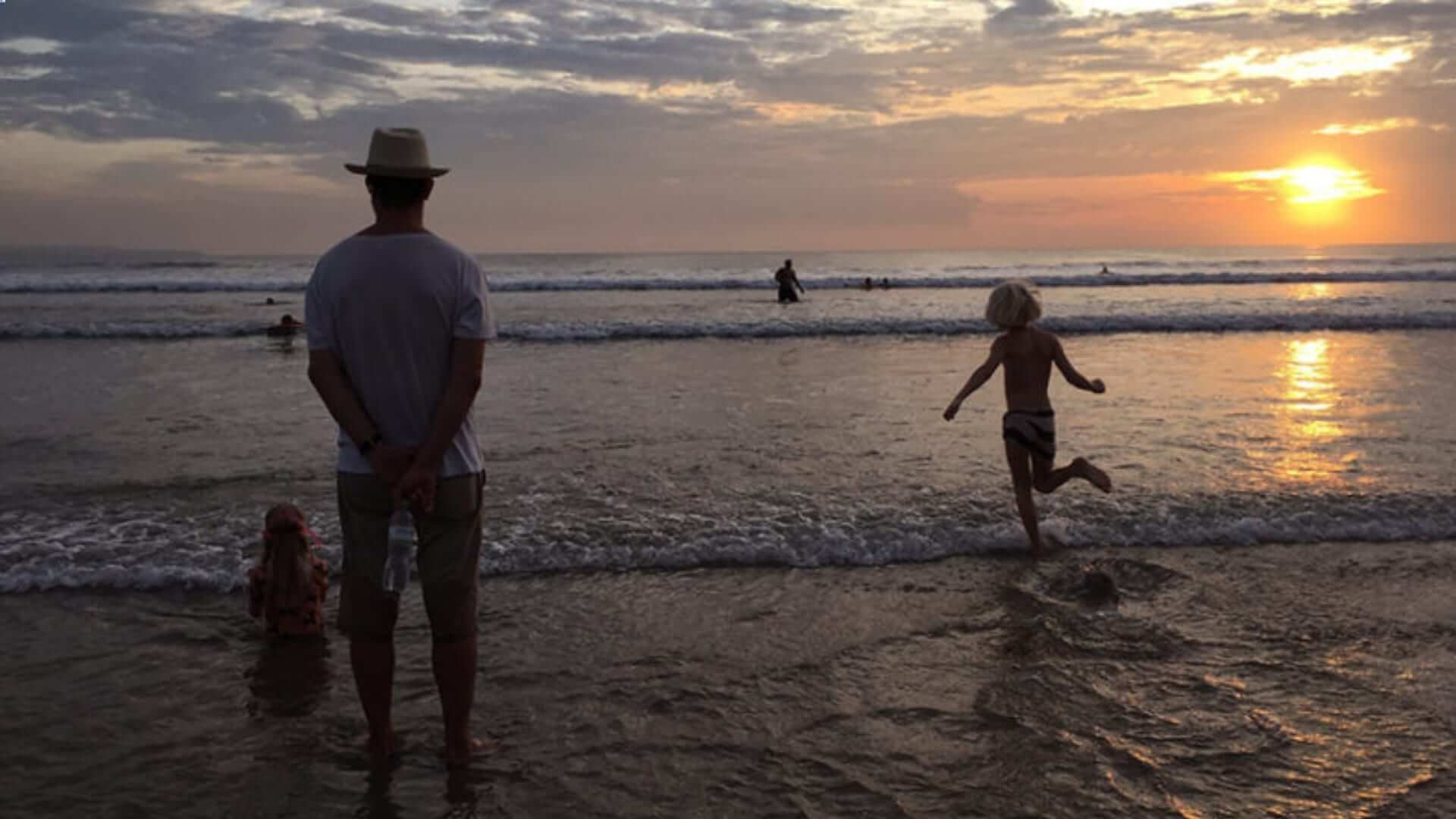 A family is standing in the water in front of the ocean looking at the sunset in Bali.