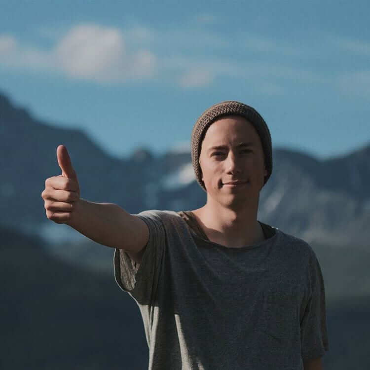 a guy in gray shirt wearing a brown bonnet showing a thumbs up