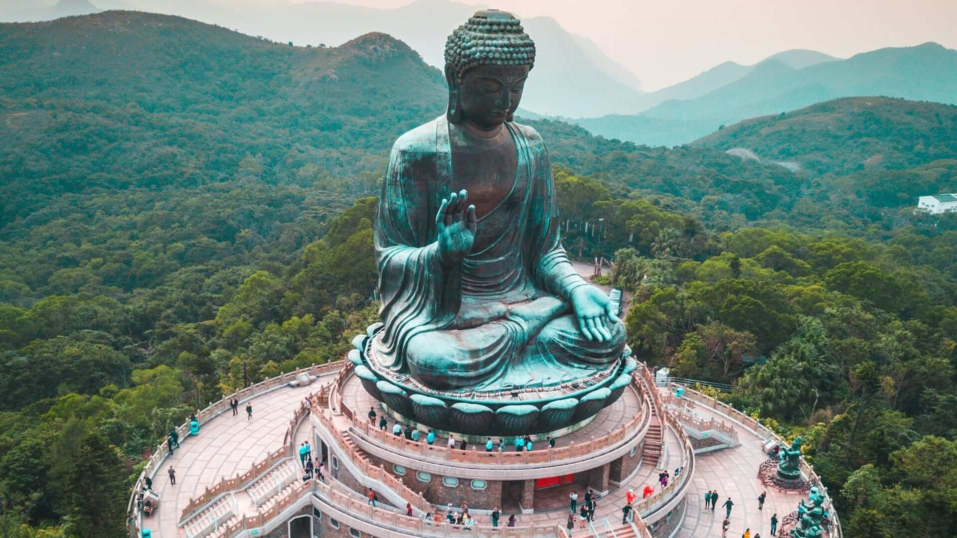 People are walking around a big buddha statue in the middle of a jungle in Hong Kong.