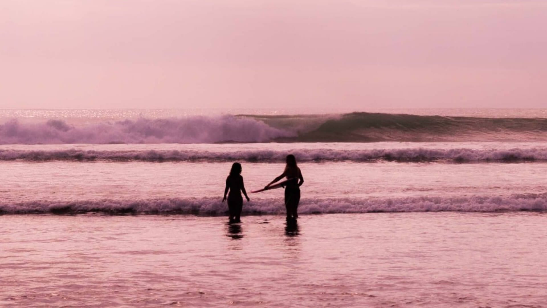 Two girls are standing in the ocean during sunset in Indonesia.