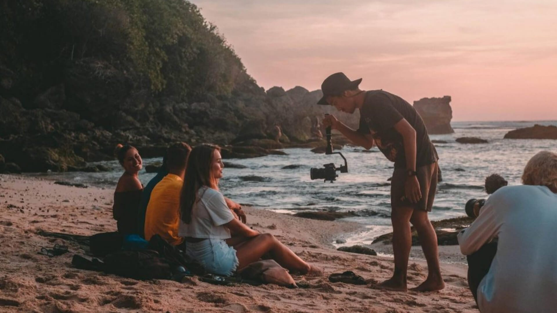 Three girls are sitting on a beach while two men are filming them during sunset in Bali.