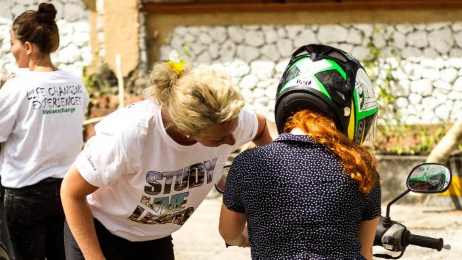 A person in white t-shirt with text is learning a student how to drive scooter in Bali.