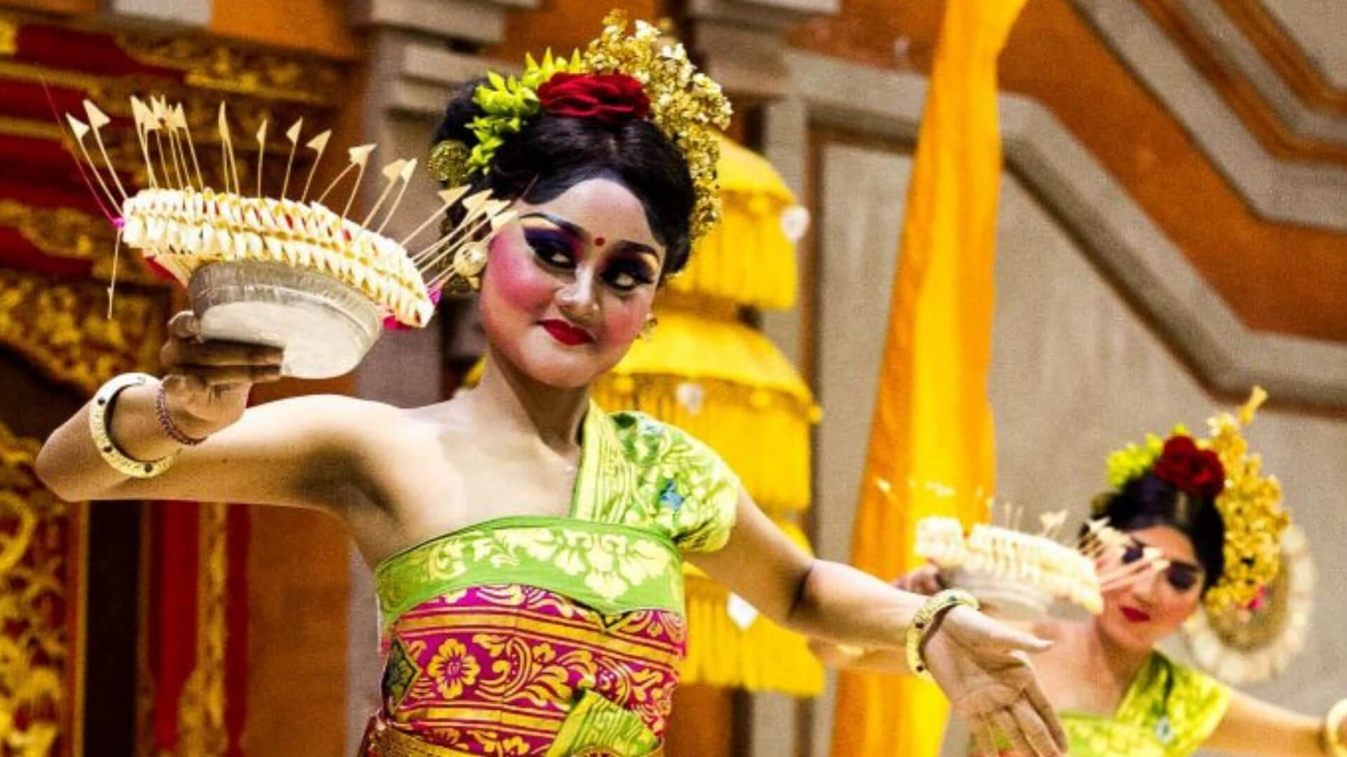 A woman wearing traditional Balinese clothes is dancing in Bali.