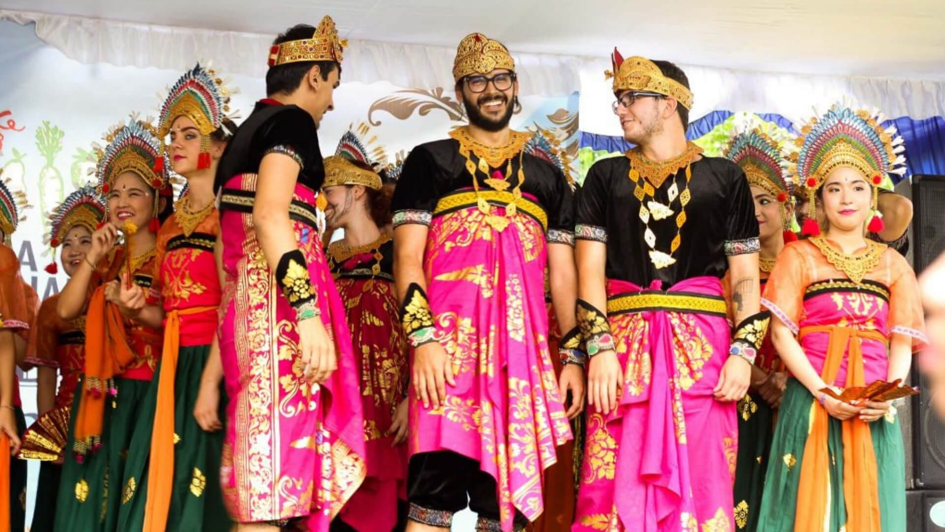 Male students are wearing traditional Balinese clothes on a campus in Bali.