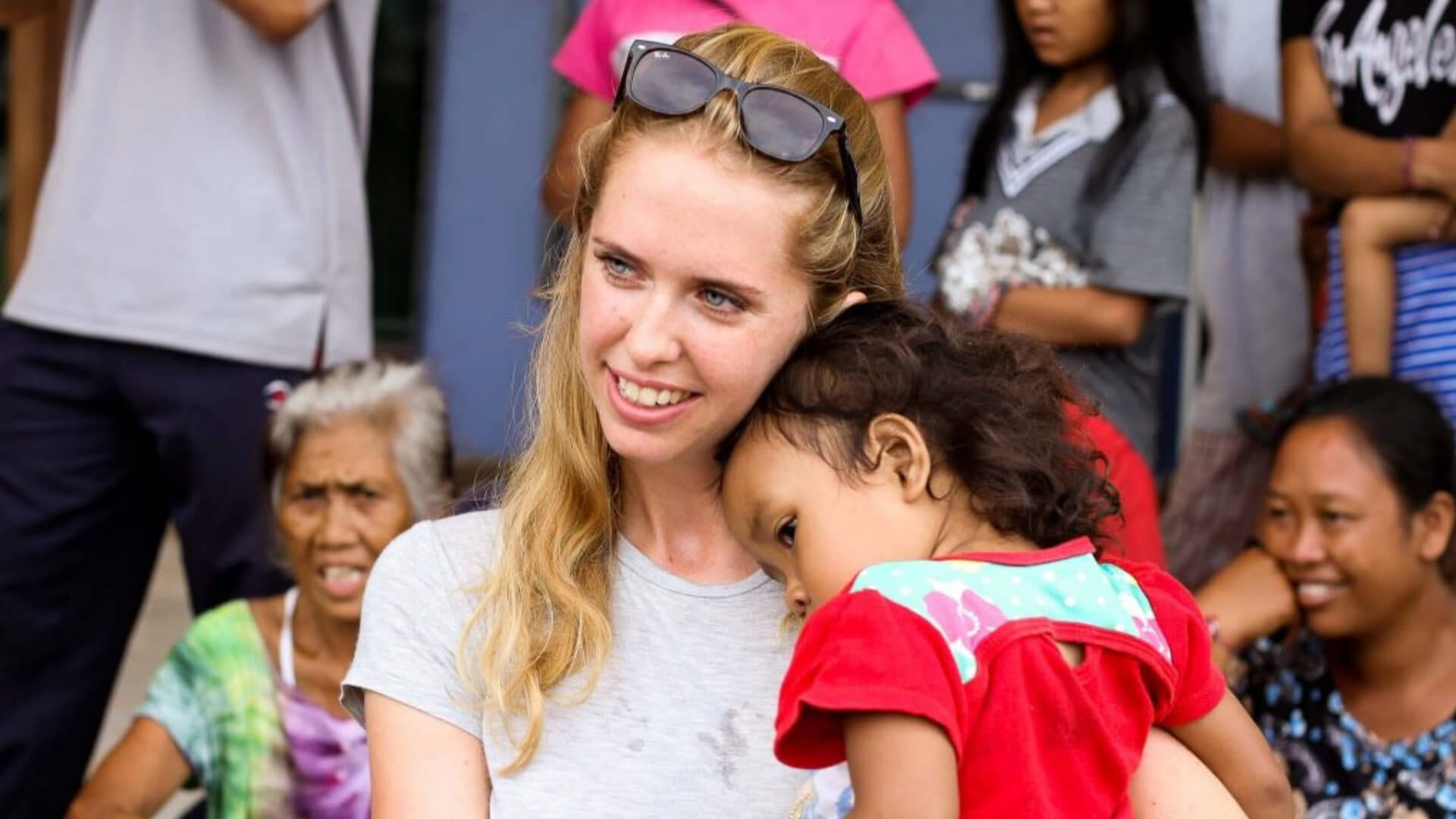 A blond girl is holding an Indonesian child that is cuddling her in Indonesia.