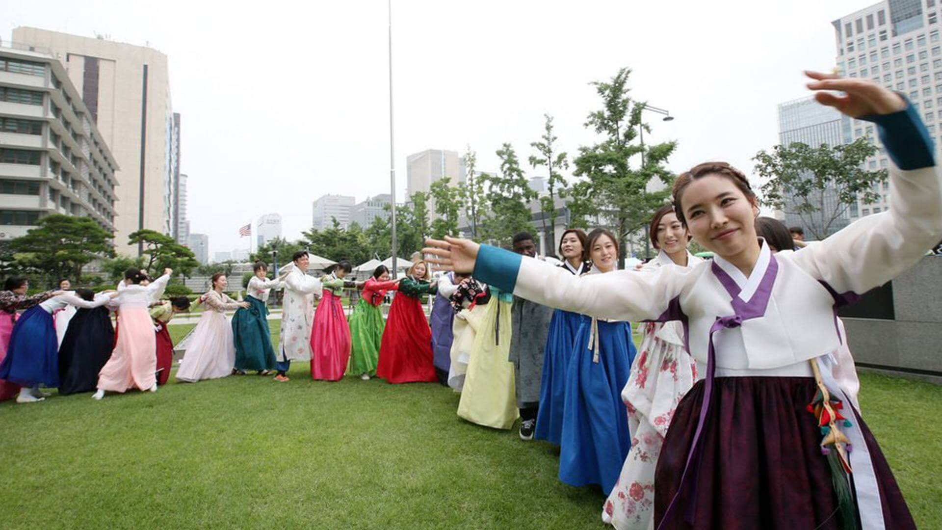Korean girls are standing in line smiling and dancing in Seoul.