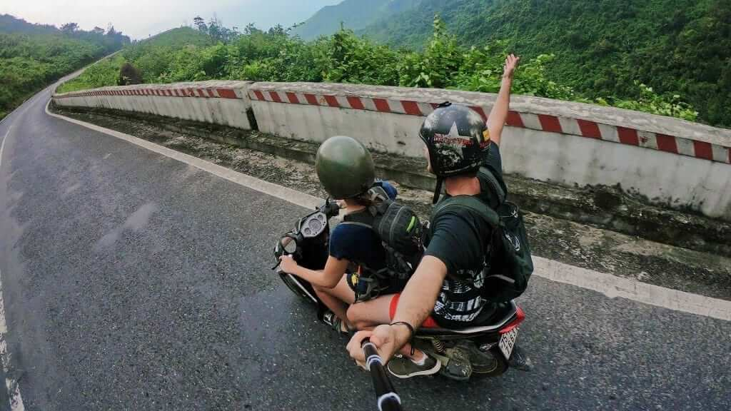 Two persons are riding a motorbike in the Bali countryside and the one in the back is holding a gopro stick