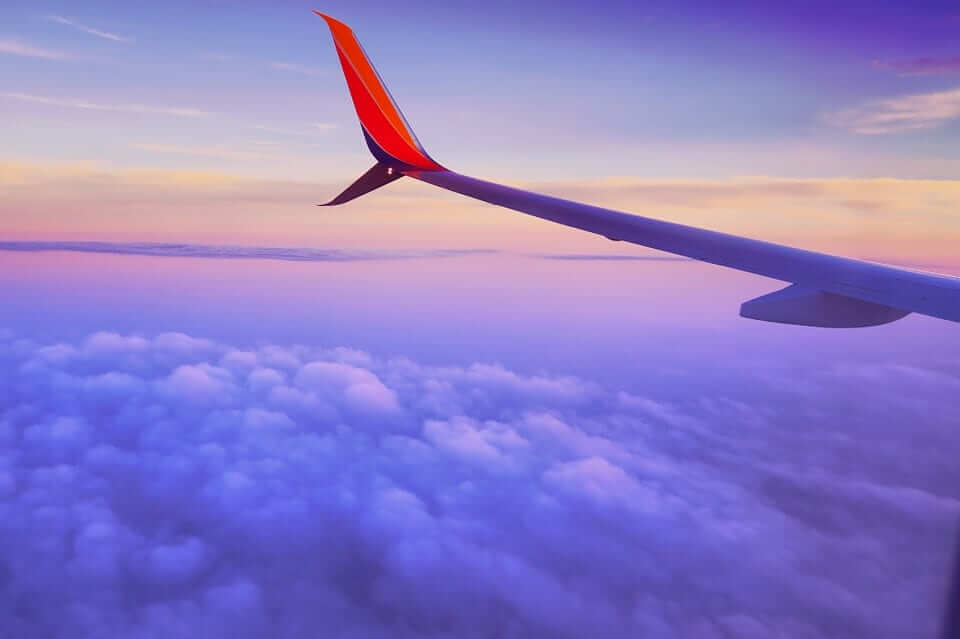 the wings of airplane along with purple skies