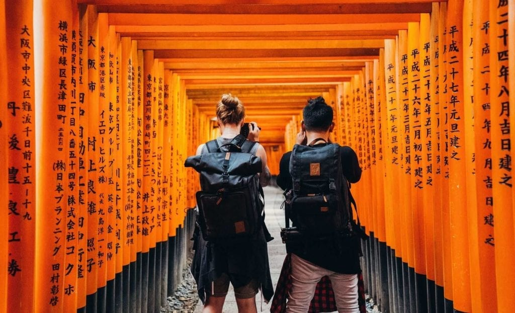 man and woman standing under orange kanji text print walls