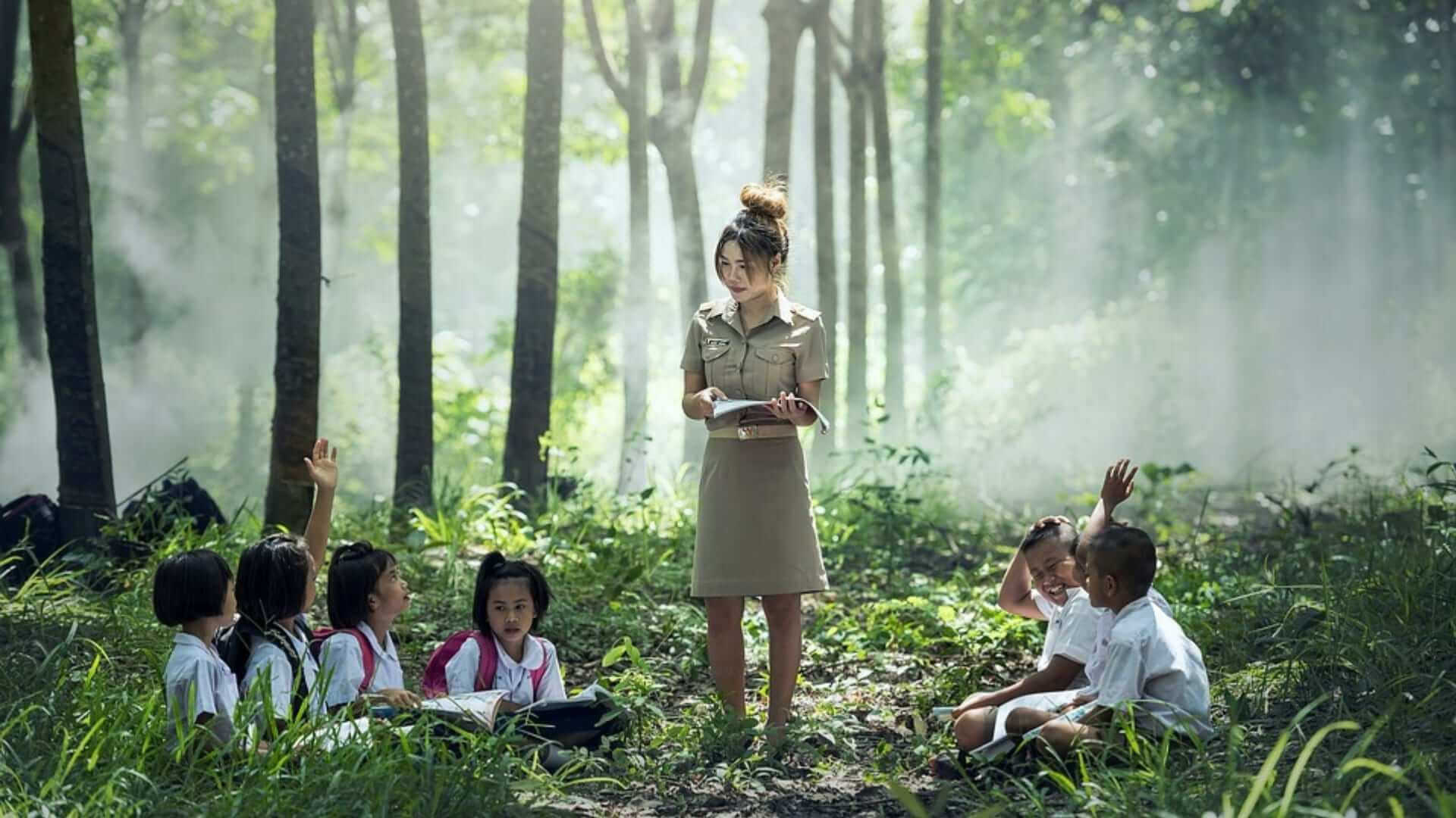 A woman is teaching children sitting in a cirkle in a forrest in Asia.