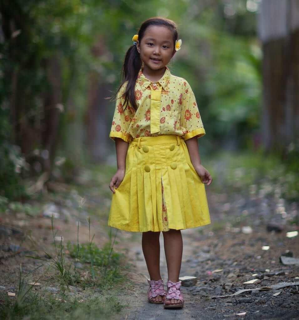 little girl wearing yellow school uniform