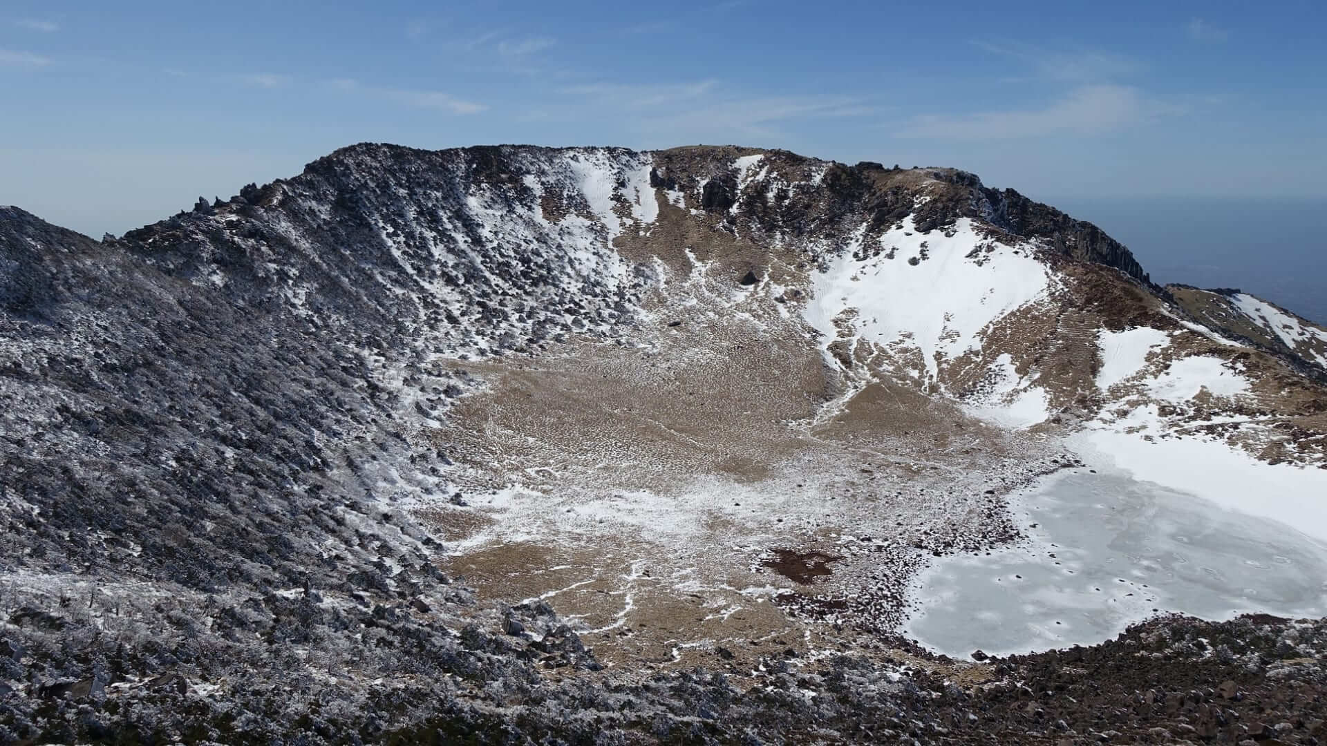 A crater with a lake and snow in it during winter on the Jeju Island.